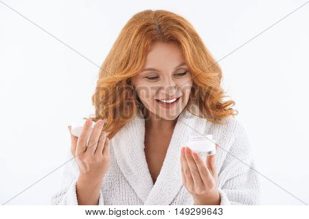Happy mature woman is looking into open cream can with interest. She is laughing. Isolated on background