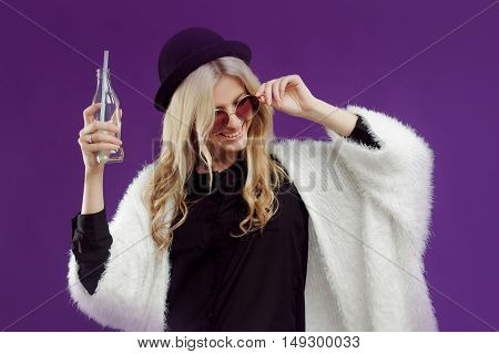 Young beautiful blonde woman in a fashionable hat. Drinking soda from glass bottles.