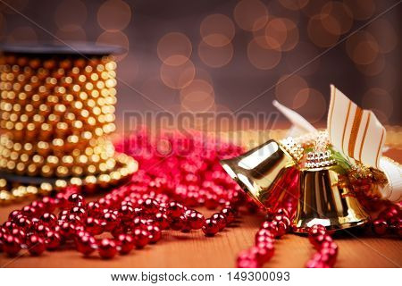 Christmas decoration. Bells and chain red and golden ornamental beads on a reel. Selective focus on the bells.