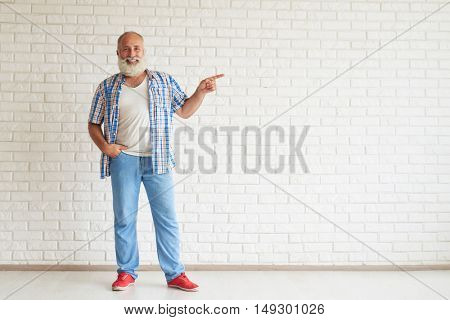 Happy senior dressed fashionably standing and points a finger in the direction, white brick wall on background