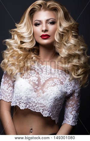 Beautiful blonde bride in wedding image with curls, red lips. Beauty face. Picture taken in the studio