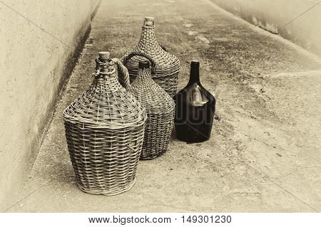 Woven wicker wine bottles. Black and white image stylized as vintage postcard.