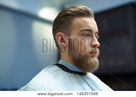 Young hipster in barber shop