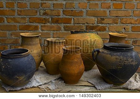 pottery clay pots standing on a wooden table on a background of a brick wall