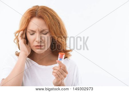 Desperate middle-aged woman suffers from headache. She is standing and touching temple with disappointment. Woman is holding pills. Isolated and copy space in right side