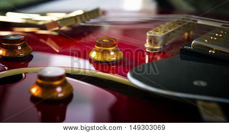 Red acoustic guitar close up in dark background