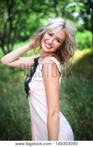 young beautiful lady outdoor portrait, woman with long blond hair posing in summer park.
