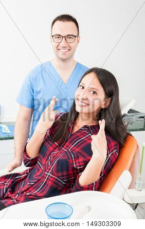 Young Lady Patient Showing Fingers Crossed On Dentist Chair