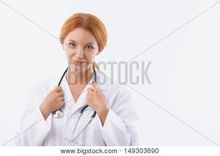 Kind female doctor is standing and smiling. She is touching stethoscope over neck. Isolated and copy space in right side