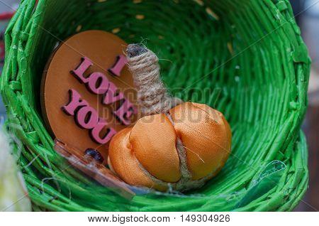 Textile handmade pumpkin in a green basket