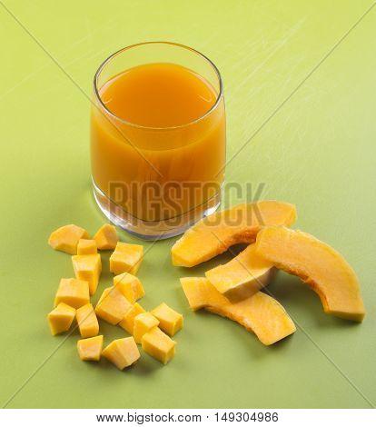 Pumpkin Juice. Pumpkin Juice In A Glass On A Green Background, The Pumpkin Is Cut Pieces.