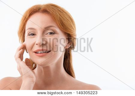 I like my skin. Joyful senior woman is standing and touching her face gently. She is looking at camera and smiling. Isolated and copy space in right side