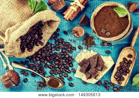 Food background in blue tone with roasted coffee beans cinnamon sticks cupcakes and chocolate