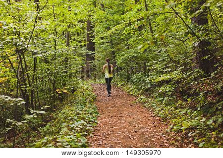 Young athletic sporty girl with long hair in green sleeveless shirt training in green forest during summer autumn season with lots of leaves fallen on forest path. Back view with copy space