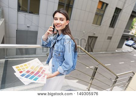 contemporary stylist holding trending colors and talking on her phone
