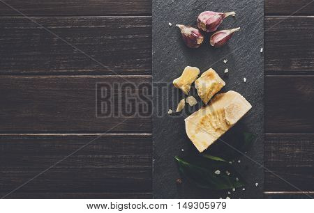 Cheese delikatessen closeup on black stone desk at wooden surface background. Parmesan pieces decorated with basil and garlic, top view image with copy space