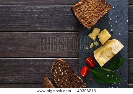 Cheese delikatessen closeup and healthy rye bread on black stone desk at wood background. Parmesan pieces decorated with basil and cherry tomatoes, top view image with copy space, soft toning