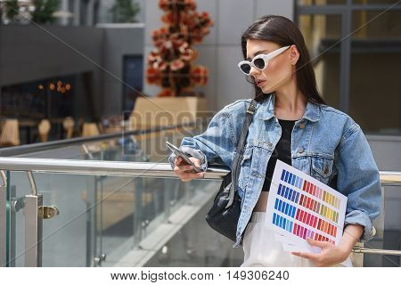 young female designer with color swatches and smartphone on the street