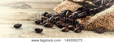 Roasted coffee beans on old wood background with copyspace. Macro shot