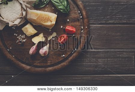 Cheese delikatessen closeup on rustic wood. Wooden desk with parmesan, camembert and brie cuts decorated with garlic, tomato and basil, top view image with copy space, soft toning