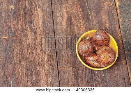 Salak fruit, Salacca zalacca in cup on the wooden floor background