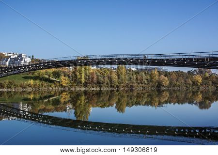Long modern pedestrian bridge above the river with reflection