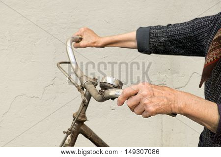 Old hands holding handlebar of a bicycle.