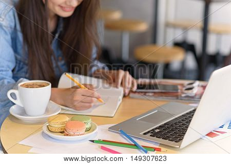 woman drawing in her notebook at her workspace in the cafeteria