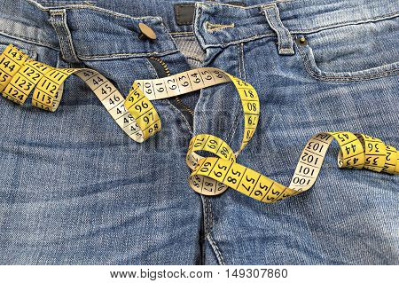 Detail of blue jeans with measuring tape.