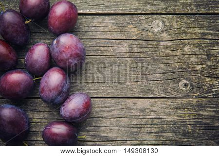 Fresh ripe plums on old wooden table. Top view.