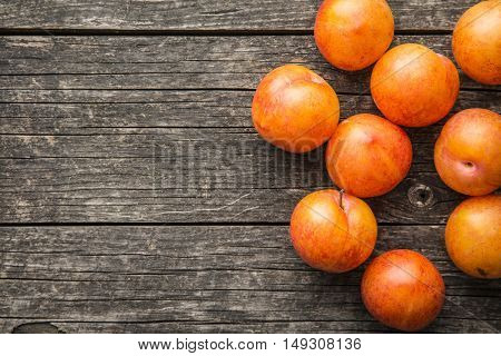Ripe yellow plums on old wooden table. Top view.