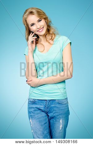 Friendly smiling young woman in casual t-shirt and jeans. Beauty, healthcare. Healthy white teeth. Studio shot.