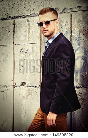 Handsome elegant man in a suit walking down the city street. Fashion shot. Business man outdoor.