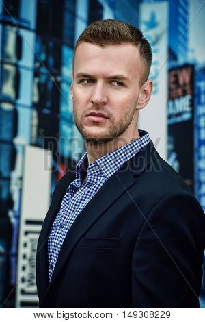 Respectable young man in a suit in the center of a big city. Fashion shot. Business style.