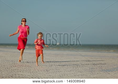 happy little boy with mother running on summer tropical beach