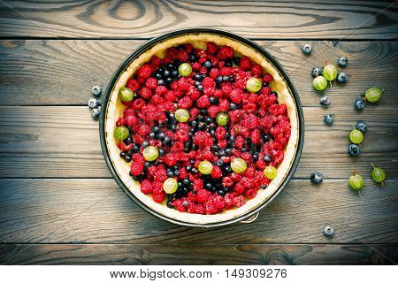 Wild berry homemade pie with fresh raspberries and blueberries on wooden rustic background