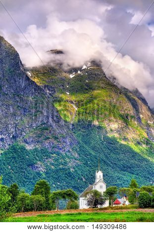 View of white wooden Oppstryn Church and mountains in Sogn og Fjordane county, Norway