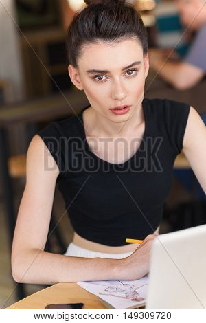 calm face of a modern girl sitting in front of a laptop