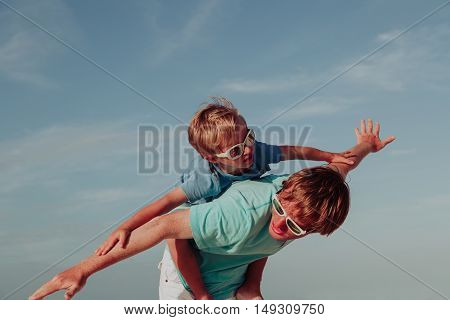 happy father and little son playing on sky