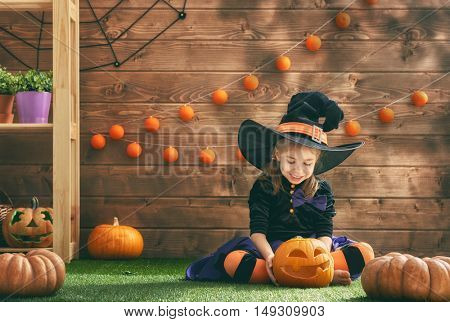 Happy Halloween! Cute cheerful little witch with a pumpkin. Beautiful child girl in witch costume sitting on grass, playing and laughing.