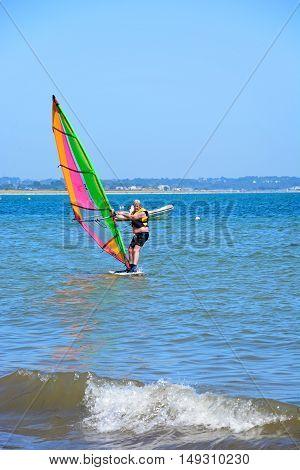 STUDLAND BAY, UNITED KINGDOM - JULY 19, 2016 - Windsurfer riding the waves near the beach Studland Bay Dorset England UK Western Europe, July 19, 2016.