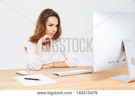 Pensive businesswoman thinking about something and looking at laptop at the office