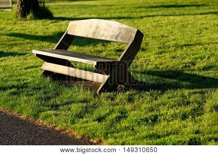 Empty wooden bench on the meadow