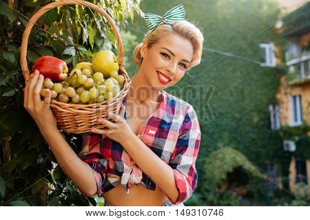 Portrait of cheerful lovely young woman holding basket of fresh fruits