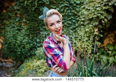Happy amazed pin up girl standing with opened mouth in the park
