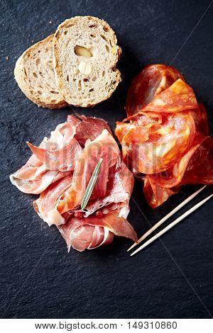 Prosciutto and chorizo on a black slate