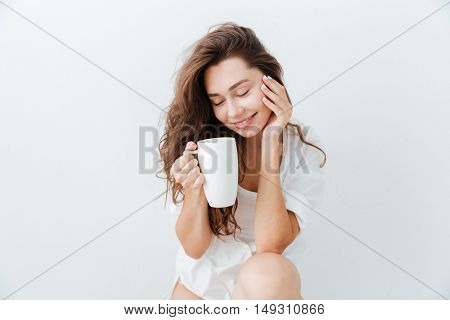 Beautiful young lovely girl with cup of tea sitting and resting isolated over white background