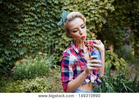 Portrait of beautiful pin up girl drinking soda in the park