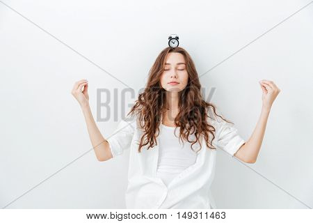 Young woman holding small clock on head and meditates isolated on a white background