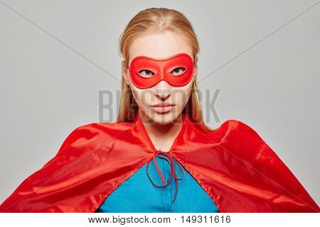 Young blond woman dressed as a superhero with a mask and a cape looking serious